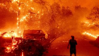 Bruce McDougal watches embers fly over his property as the Bond Fire burns through the Silverado community in Orange County, Calif., Dec. 3, 2020.