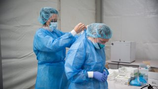 Members of the One Medical Group Inc. medical staff put on personal protective equipment