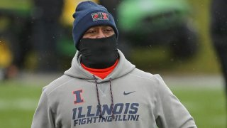 Illinois head football coach Lovie Smith, wearing a gray hooded sweatshirt, black gaiter mask and blue stocking cap, walks across the field before a game against Northwestern University