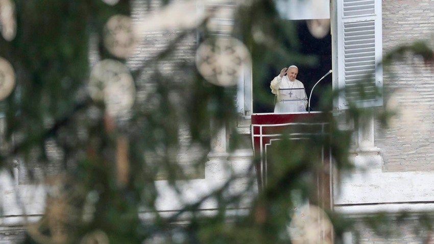 Pope Francis, framed by a Christmas tree, waves as he arrives to recite the Angelus noon prayer from the window of his studio overlooking St.Peter's Square, at the Vatican, Dec. 6, 2020.