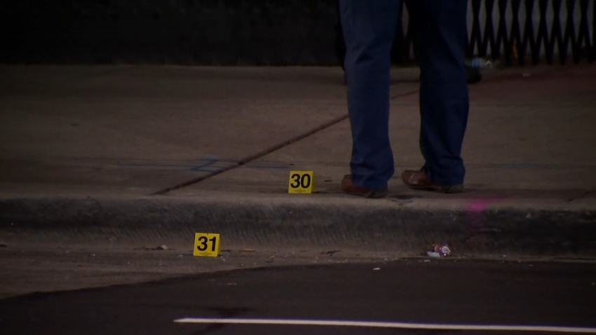 A Chicago police officer stands next to evidence markers outside of a shooting scene in the city's Burnside neighborhood on Dec. 19, 2020