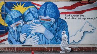 A health worker wearing a personal protective equipment walks past an alley with a mural illustrating medical frontliners outside Clinic Ajwa in Shah Alam, Malaysia.