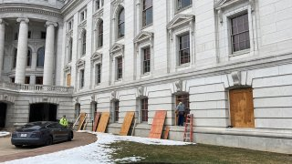 Workers begin boarding up the Wisconsin state Capitol building in Madison on Monday, Jan. 11, 2021. State officials are concerned about the prospects of state-centered violence in the wake of last week's security breaches at the U.S. Capitol.