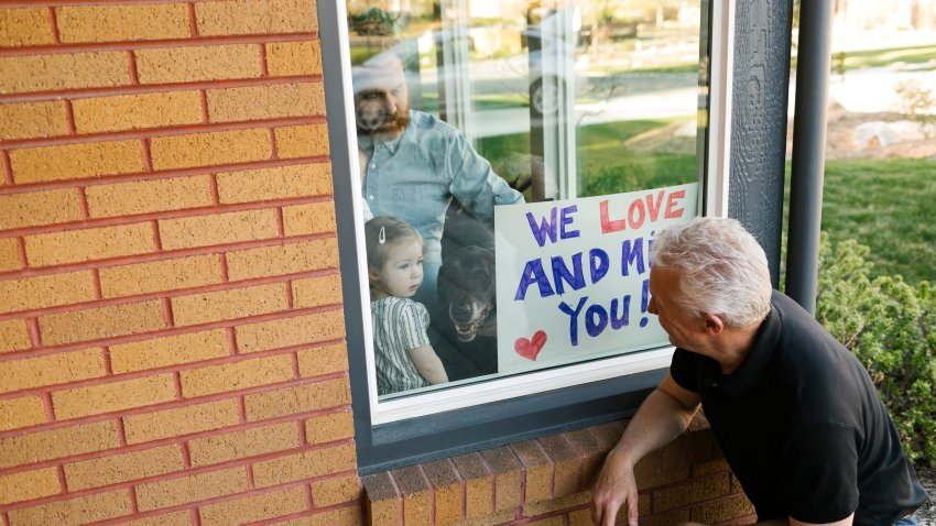 Grandfather visiting family with granddaughter (2-3) through window