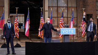 Flanked by U.S. Democratic Senate candidates Rev. Raphael Warnock (L) and Jon Ossoff (R), U.S. President-elect Joe Biden gestures to the crowd at the end of a drive-in rally at Pullman Yard on December 15, 2020 in Atlanta, Georgia. Biden's stop in Georgia comes less than a month before the January 5 runoff election for Ossoff and Warnock as they try to unseat Republican incumbents Sen. David Perdue and Sen. Kelly Loeffler.