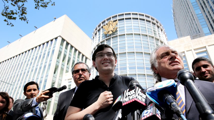 Martin Shkreli, former chief executive officer of Turing Pharmaceuticals AG, center, while his attorney Benjamin Brafman, right, speaks to members of the media outside federal court in the Brooklyn borough of New York, U.S., on Friday, Aug. 4, 2017.