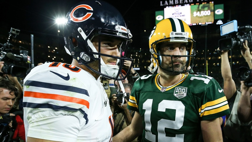 Bears quarterback Mitchell Trubisky, wearing a white jersey and the team's signature navy blue helmet, greets Packers quarterback Aaron Rodgers, who is wearing the Packers' gold helmet and a green jersey, after a 2019 game at Lambeau Field