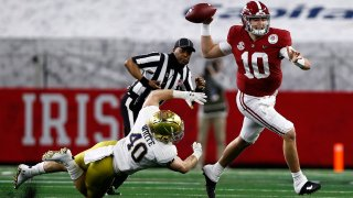 Quarterback Mac Jones #10 of the Alabama Crimson Tide delivers a pass over linebacker Drew White #40 of the Notre Dame Fighting Irish during the first quarter of the 2021 College Football Playoff Semifinal Game at the Rose Bowl Game presented by Capital One at AT&T Stadium on January 01.