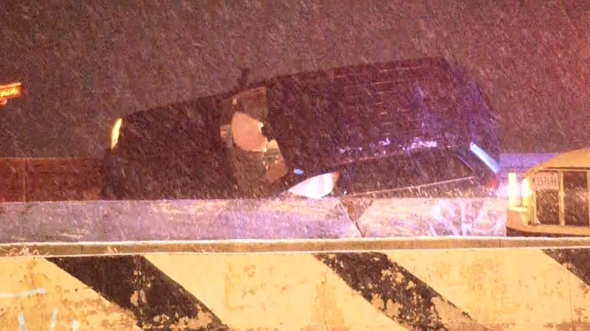 A black SUV, with air bags deployed, is shown behind a concrete barrier on Lake Shore Drive, with snow falling in the foreground