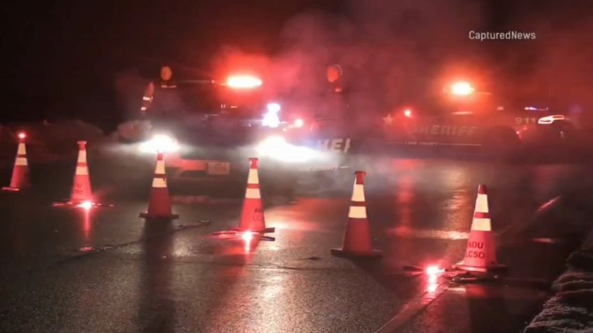 Lake County sheriff's deputies examine a shooting scene in Volo; pictured are two police cars, with red lights flashing and fog rising from the street, along with red road flares and orange traffic cones
