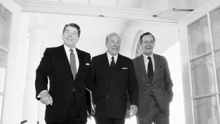Secretary of State George Shultz, center, walks with President Ronald Reagan and Vice President George Bush