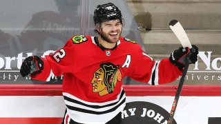 """Blackhawks forward Alex DeBrincat, wearing a red jersey with an """"A"""" on the left shoulder, celebrates after scoring a game winning goal against Columbus"""