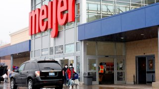 People wear face masks as they leave a Meijer store