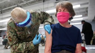 In this Feb. 3, 2021, file photo, Sergeant Jennifer Callender (L) of the Illinois Air National Guard administers a Pfizer Covid-19 vaccine to Virginia Persha at a vaccination center established at the Triton College in River Grove, Illinois.