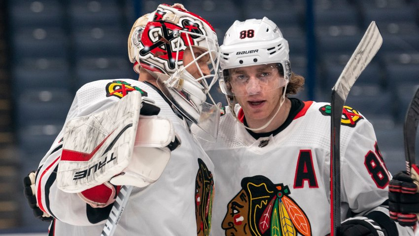Kevin Lankinen and Patrick Kane, both wearing white Blackhawks jerseys, congratulate one another on a win over the Blue Jackets