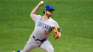 Cubs pitcher Rowan Wick, seen here wearing a blue hat with a gray jersey and gray pants, delivers a pitch against the Brewers