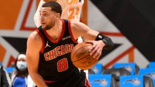 Zach LaVine, wearing a black and red Bulls jersey, dribbles a ball against the Orlando Magic
