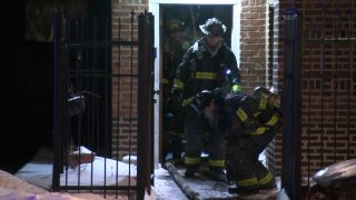 Chicago firefighters, dressed in black and yellow uniforms, walk out of a building as they fight a blaze on Feb. 14 in the city's Oakland neighborhood