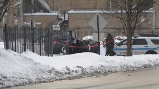 A black vehicle is pictured flipped over after it hit a Chicago police cruiser in the Englewood neighborhood