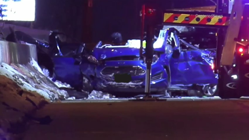 A blue Ford Fiesta, with the roof torn off and airbags deployed, sits at the scene of a fatal crash that left four people dead