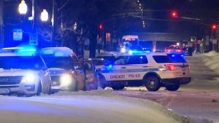 Chicago police cars are parked on a street, with lights on, as they investigate a shooting on the city's South Side