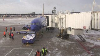 A blue Southwest Airlines jet pulls up to a gate at Chicago's O'Hare Airport on Sunday