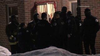 Chicago police stand outside of a residence in the city's Bronzeville neighborhood after a man attacked a woman and two children with a knife