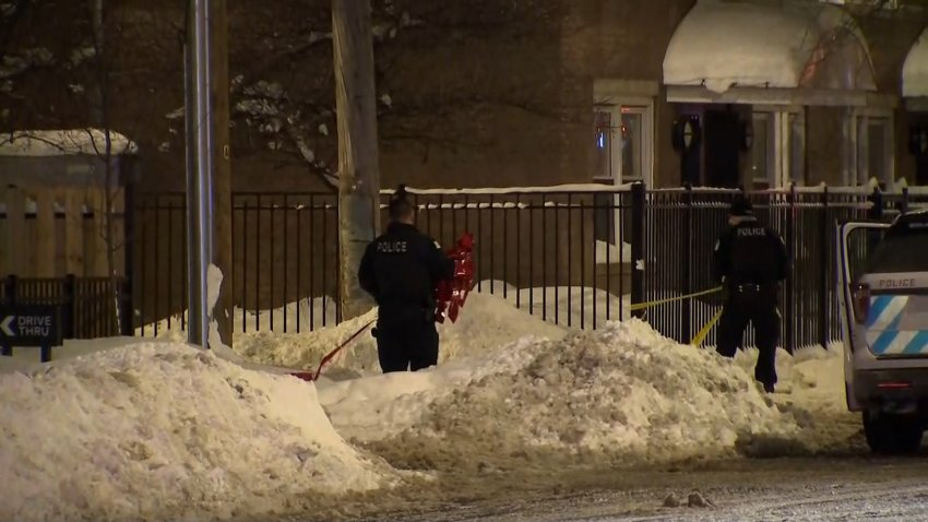 Chicago police officers stand in a snow drift, holding red crime scene tape at the scene of a fatal shooting in Bridgeport