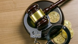 A gavel, handcuffs and cryptocurrency