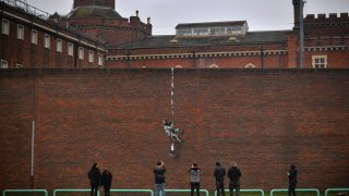 Members of the public pause to look at an artwork bearing the hallmarks of street artist Banksy
