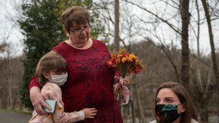 Margaux Irvine (L) the daughter of Chris Irvine, who passed from Covid-19 in January hugs her grandmother Sue, as her mother Carly (R) looks on near the James river in Lynchburg, Virginia on March 13, 2021