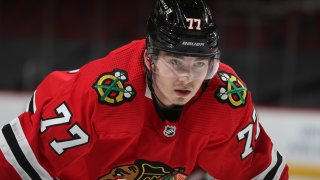 Blackhawks center Kirby Dach, wearing a red jersey and a black helmet, prepares for a face-off