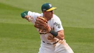 Jake Lamb, wearing a white jersey with green and gold lettering and a green Oakland Athletics cap, fields a ground ball