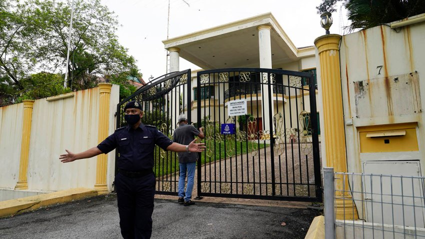 A staff member locks the front gate of the North Korean embassy in Kuala Lumpur, March 21, 2021.