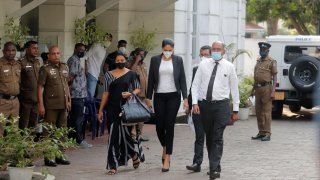 Mrs. World 2019 Caroline Jurie, center, leaves a police station after obtaining bail in Colombo, Sri Lanka