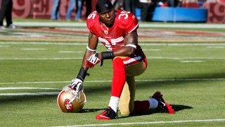 Phillip Adams on one knee