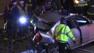 Chicago police examine the mangled remains of a gray car after a fatal crash on the Dan Ryan Expressway