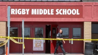 Photo of officer exiting Rigby Middle School with caution tape