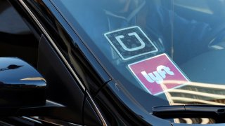 a ride share car displays Lyft and Uber stickers