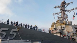 In this photo provided by the U.S. Navy, sailors aboard the guided missile destroyer USS Stout handle mooring lines during the ship's return to home port at Naval Station Norfolk, in Norfolk, Va., in this Oct. 12, 2020, photo. The USS Stout showed rust as it returned from the 210-day deployment. The rust was quickly removed and the ship repainted. But the rusty ship and its weary crew underscored the costly toll of deferred maintenance on ships and long deployments on sailors.