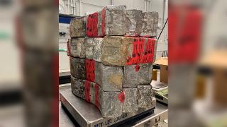 Seized drug bundles containing 132 pounds of methamphetamine on display