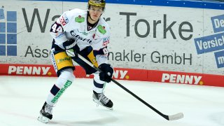 Lukas Reichel, wearing a white jersey and yellow hockey pants, skates with the puck during a German hockey league game