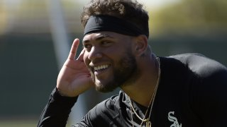 White Sox infielder Yoan Moncada smiles and puts his hand to his ear, gesturing to to a teammate during spring training