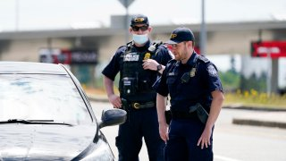 Customs and Border Protection officers direct a driver on who missed the last turn before entry into Canada on how to turn around at the Peace Arch border crossing into the U.S., Tuesday, June 8, 2021, in Blaine, Wash. The border has been closed to nonessential travel since March 2020.