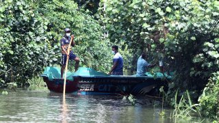 People row a boat to distribute food to flood-trapped villagers on the outskirts of Colombo, Sri Lanka, on June 5, 2021. The death toll from Sri Lanka's inclement weather conditions rose to 10 Saturday evening while 219,027 people were affected, the country's Disaster Management Center said.