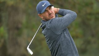 Golfer Brooks Koepka, clad in a blue hat and a blue windbreaker, finishes his swing with an iron during competition at the Travelers Championship