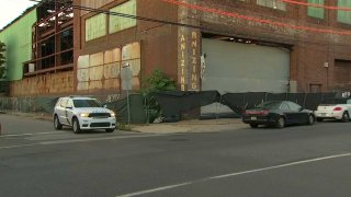 A police SUV and a sedan are parked in front of a warehouse. Philadelphia police said the sedan fell on top of a man and crushed him to death.