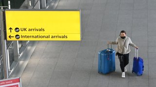 A passenger with luggage is seen at London Heathrow Airport