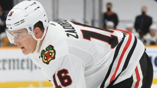 Blackhawks defenseman Nikita Zadorov stands on the ice during a game, wearing a white jersey, white helmet and black hockey pants