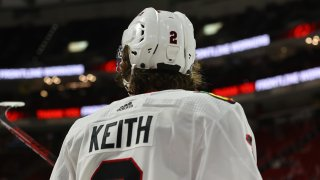 Blackhawks defenseman Duncan Keith, wearing a white jersey with black lettering and a white helmet, stands with his back to the camera during a game